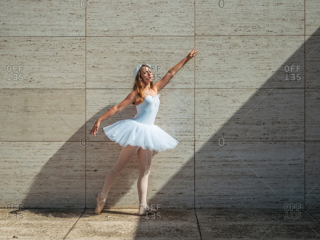 Ballerina in white ballet tutu performing exercises in classroom in contrast sunny light