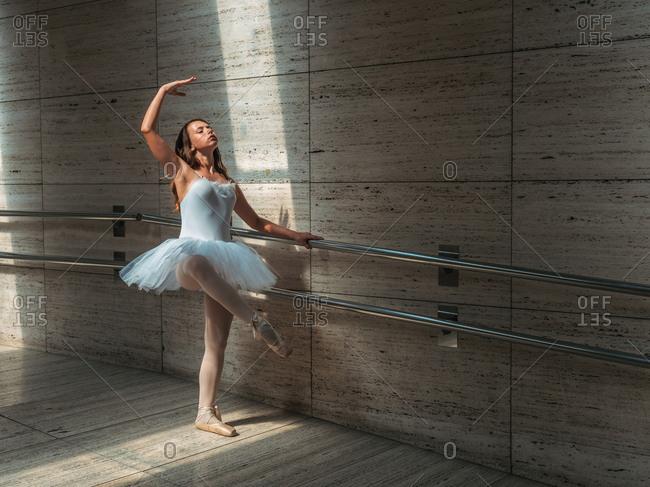 Ballerina in white ballet tutu performing exercises at rail in contrast sunny light