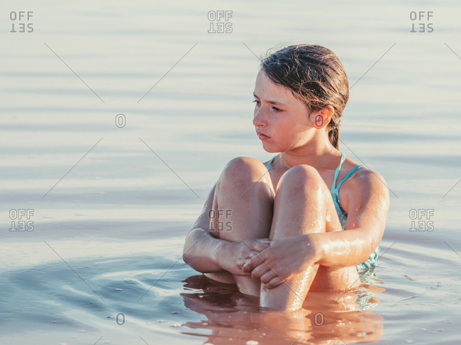 Thoughtful girl staying in crystal water with folded hands in hot day