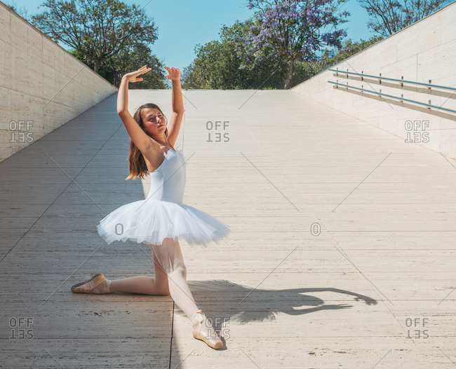 Classical ballet position gracefully performing by ballerina with raising hands and stretching legs outside in bright sunny day