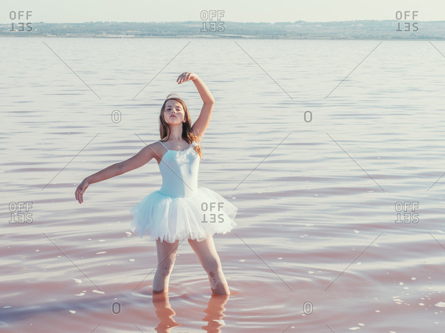 Classical ballet position gracefully performing by ballerina with raising hands in fresh wavy water in bright sunny day