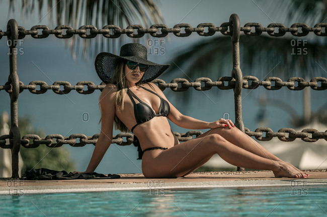 Woman in swimsuit sitting by pool with turquoise water