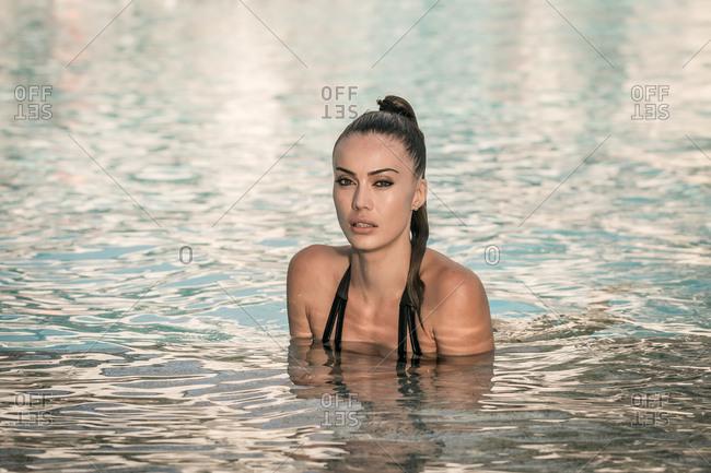 Slim woman in bikini in pool looking at camera