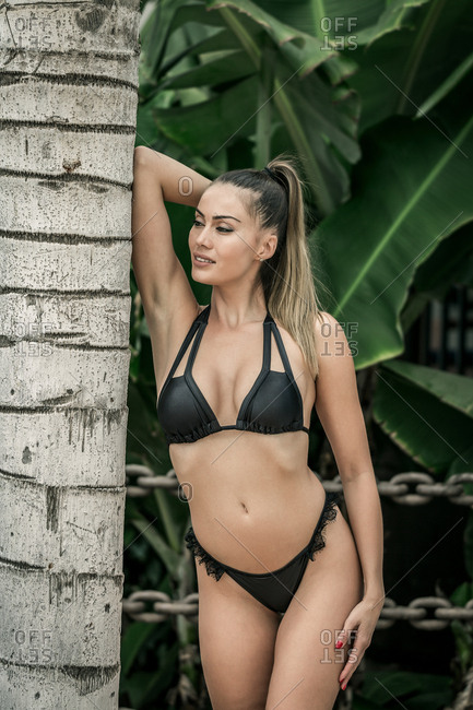 Attractive sporty woman in black swimsuit enjoying sunny day leaning tree in exotic place