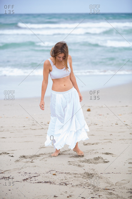 Beautiful attractive female in white outfit dancing on sand near waving sea