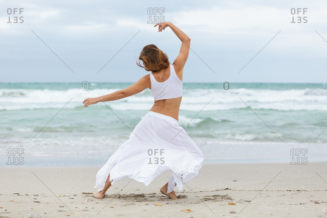 Back view of unrecognizable female in white outfit dancing on sand near waving sea