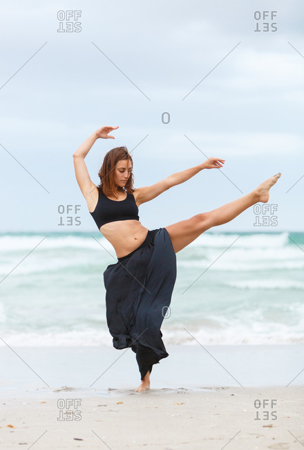 Beautiful attractive female in black outfit dancing on sand near waving sea