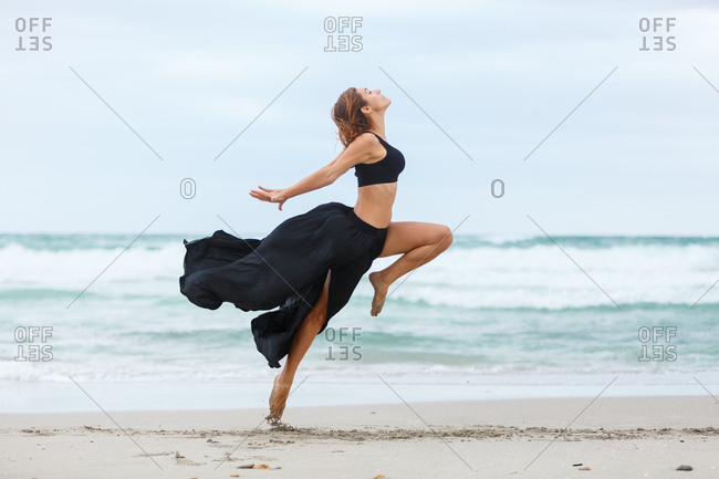 Side view of beautiful attractive female in black outfit dancing on sand near waving sea