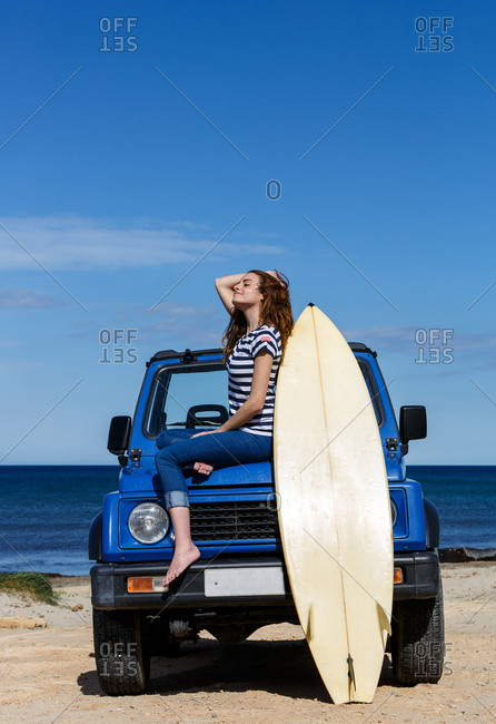 Attractive long haired woman sitting on top of a blue offroadster car with big surfboard in bright day