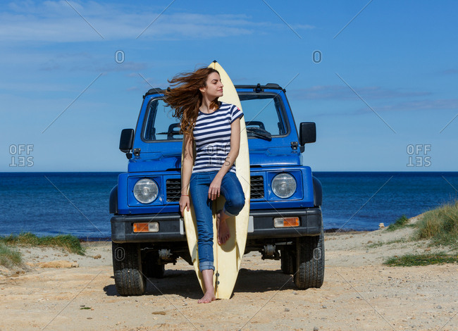 Attractive long haired woman looking at camera standing leaning on surfboard near to blue offroadster in bright day
