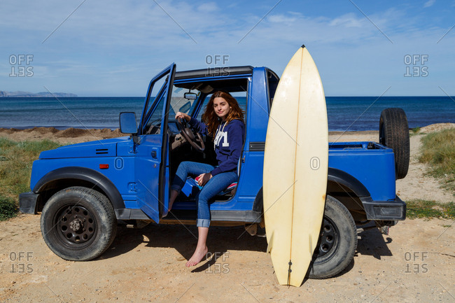 Attractive long haired woman sitting in blue offroadster with open door and surfboard on background of serene seascape