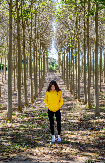 Beautiful young female standing in yellow sweatshirt on nature background and looking down