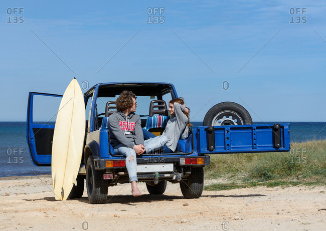Young energetic couple with surfboard sitting on the back of blue offroadster in bright day