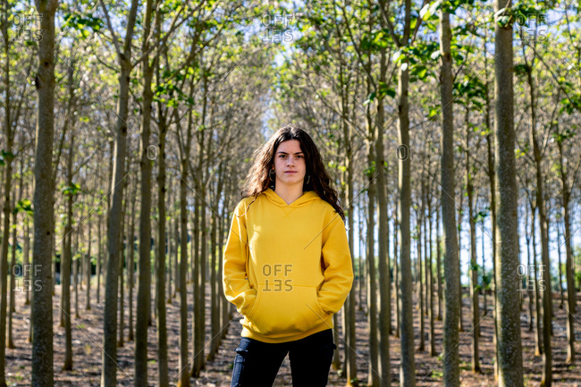 Beautiful young female with long black hair standing in yellow sweatshirt on nature background and looking at camera