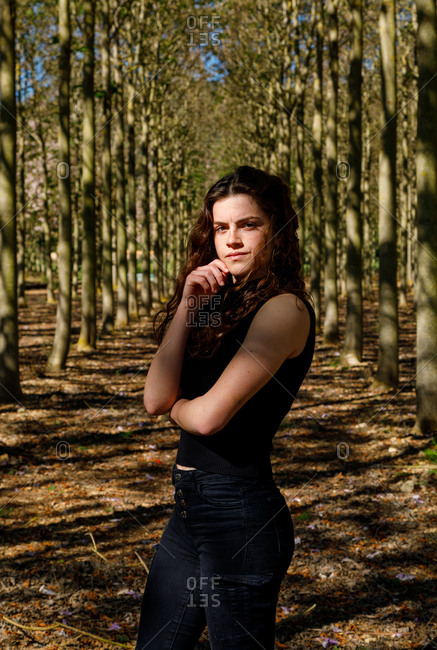 Beautiful young female standing in beautiful wood forest full of tall trees on the background and looking at camera
