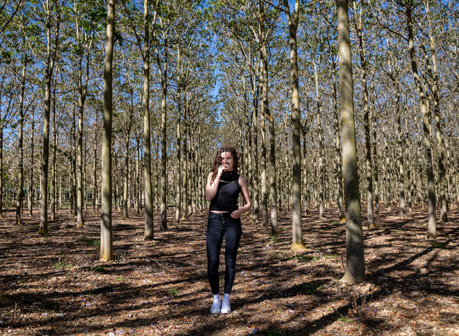 Beautiful young female standing in beautiful wood forest full of tall trees on the background and looking away