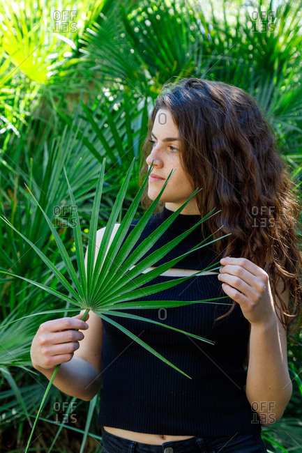 Attractive brunette woman standing in tropical bushes and looking away holding a palm tree leaf
