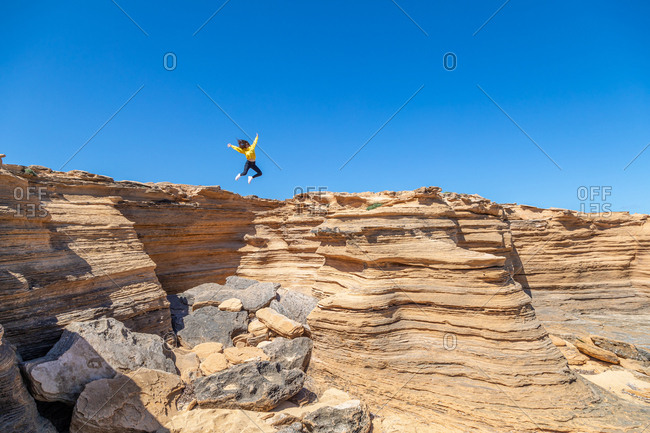 Young woman in yellow sweatshirt jumping with spread hands over deserted sandstone rocks on sunny day