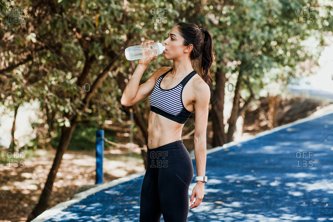 Beautiful fit woman in sportswear drinking water from a bottle after jogging on running track on summer day