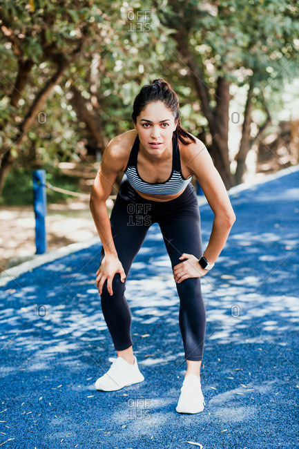 Beautiful fit woman in sportswear standing with resting pose while jogging on running track on summer day