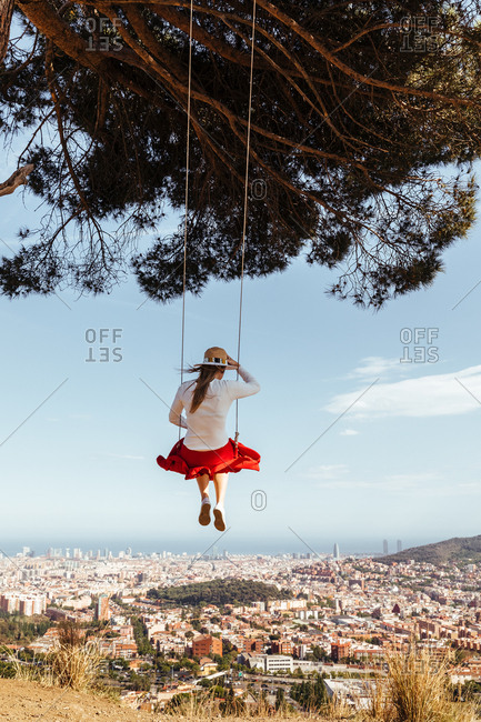 Girl having fun with red skirt and hat swinging while contemplating the city in the background