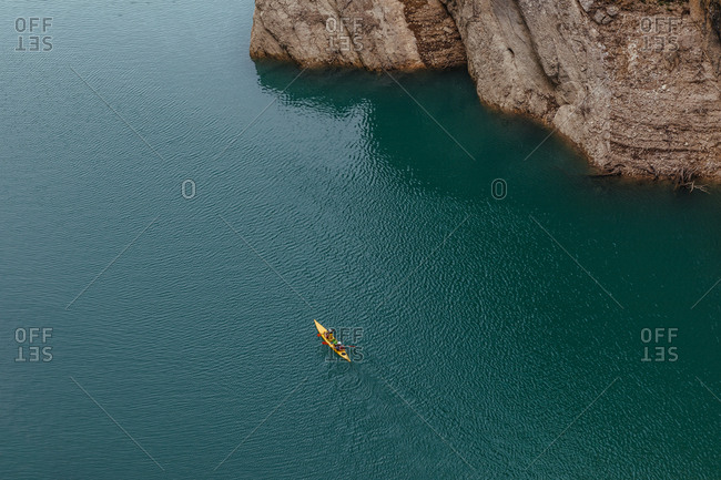 Unrecognizable people kayaking in the middle of the river