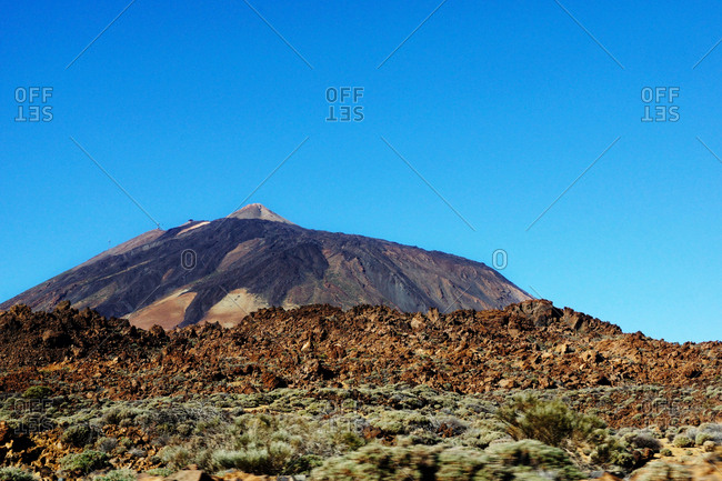 Volcano of Teide and burnt wild area of Tenerife, Spain on background of clear blue sky