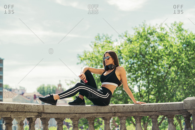 Side view of young athletic brunette woman in sportswear sunglasses and headphones sitting with smartphone on stone balcony fence