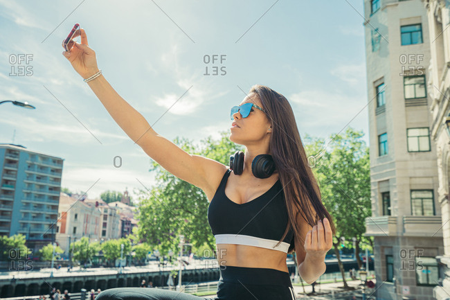Side view of young athletic brunette woman in sportswear sunglasses and headphones taking selfie on smartphone on stone balcony fence