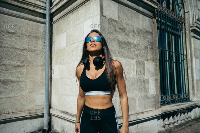 Young confident athletic brunette woman in sportswear sunglasses and headphones demonstrating sport figure outside
