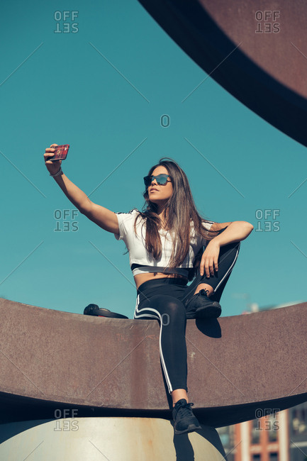 Young athletic brunette woman in sportswear sunglasses and headphones taking selfie with smartphone sitting on metallic structure