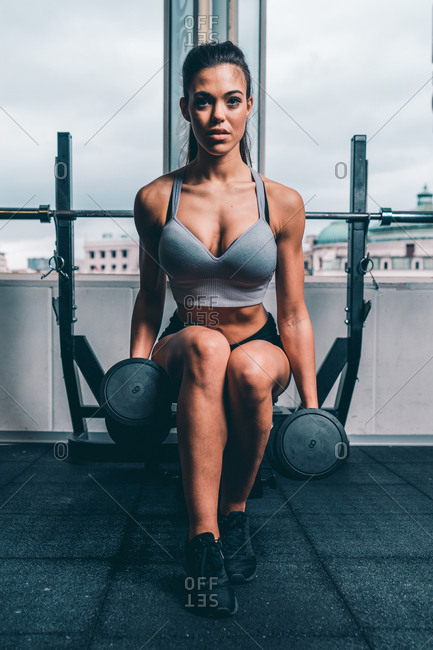 Front view of young athletic woman in sportswear picking up big heavy dumbbells in gym while sitting on bench