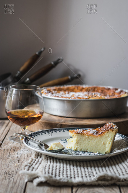 Cottage cheese baked pudding served on plate and glass of cognac on towel against wooden table