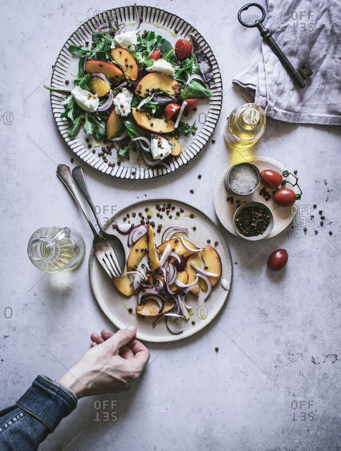 From above crop hand of man holding plate with summer salad made of fruits, vegetables and spices