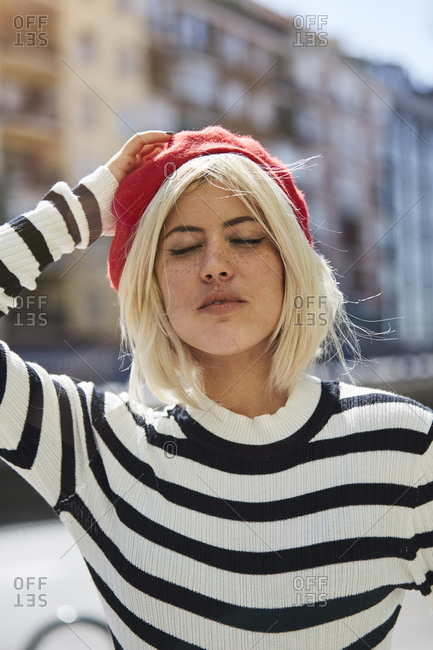 Young blonde woman in striped black and white shirt and red French cap on blurred background