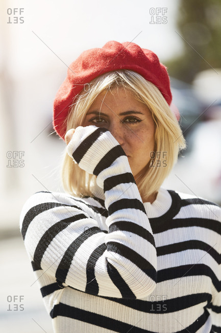 Young blonde woman in striped black and white shirt and red French cap on blurred city background