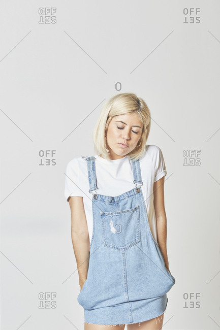 Beautiful young woman in white t-shirt and jeans sundress standing on grey background and looking down