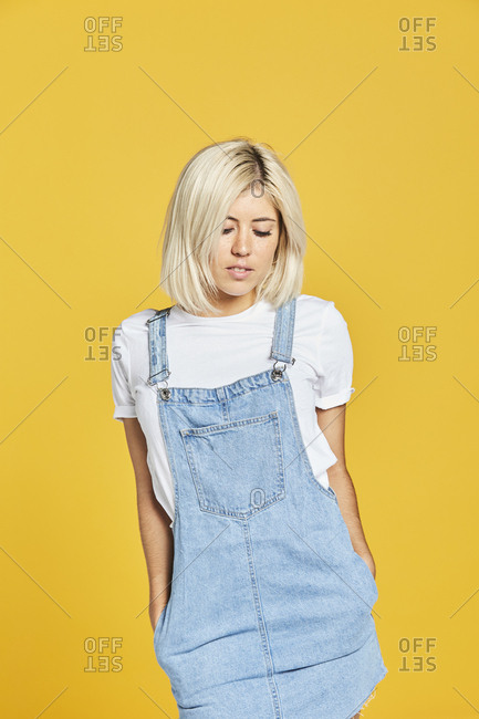 Beautiful young woman in white t-shirt and jeans sundress standing on yellow background and looking down