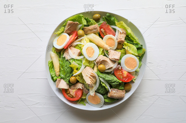 From above bowl of fresh salad with lettuce, tuna, tomatoes, eggs, onion and olives on white texture background