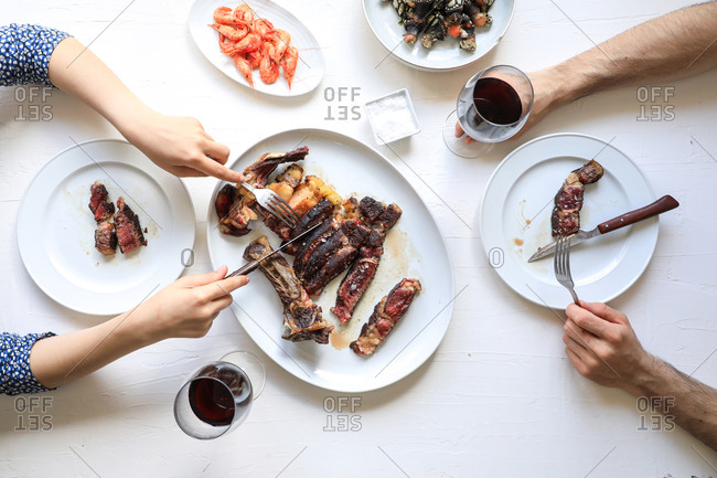 From above crop people cutting meat steak and enjoying red wine while eating tasty meal