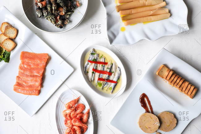 From above appetizing meal with cooked shrimps, salmon, marinated fish and toasts arranged on white background