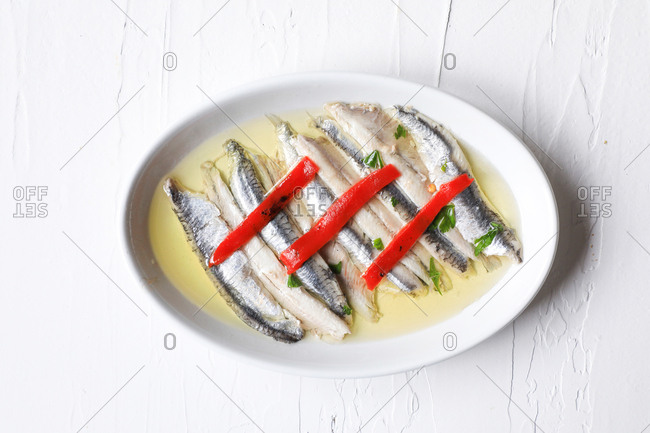 From above marinated sardines with red pepper, oil and parsley served on white texture background