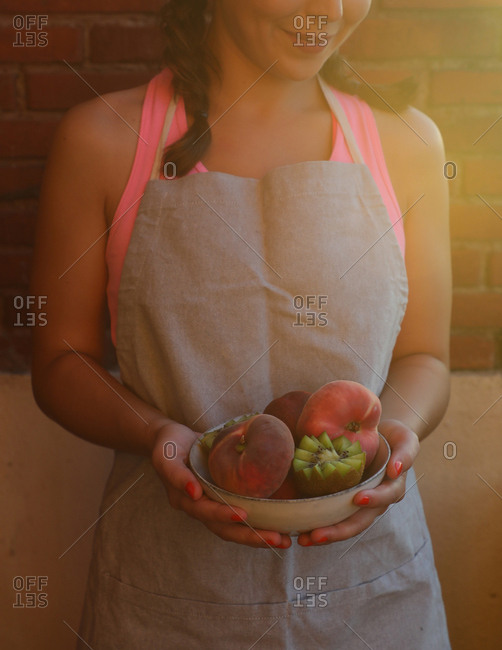 Tasty appetizing peaches and cut ripe juicy kiwi in bowl in hands of smiling woman in apron