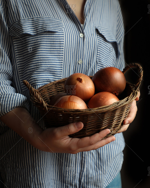 Shiny appetizing onion in peel in brown straw-plaited basket in hands