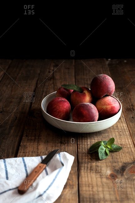 Appetizing bright peaches with leaves in white plate on wooden table and knife on cloth napkin