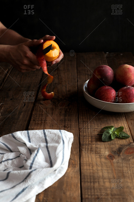 Side view of hands peeling peach and appetizing bright peaches in white plate on wooden table with cloth napkin