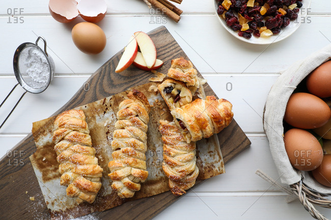 From above delicious fresh strudels with sweet apples and raisins placed on white tabletop near sieve and raw eggs