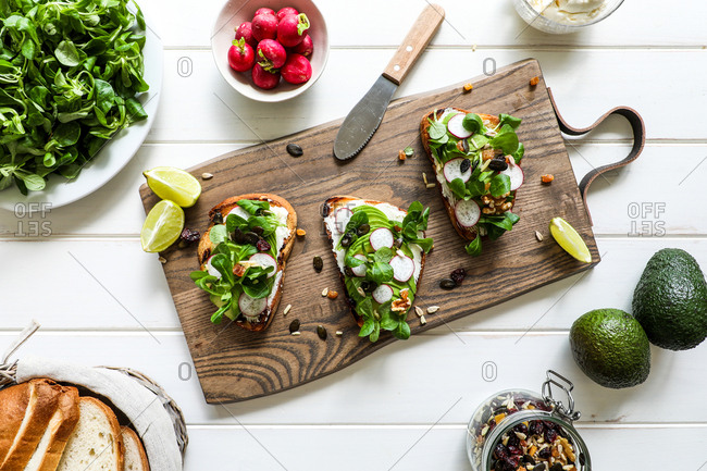 From above toasts with assorted vegetables placed on wooden cutting board on white tabletop