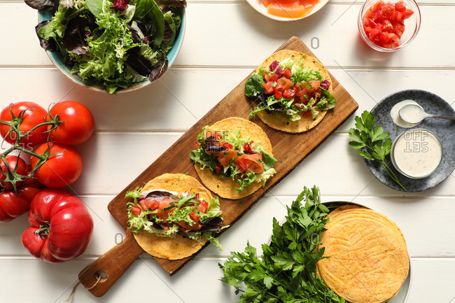 From above wooden cutting board with tasty vegetarian tacos placed on white tabletop