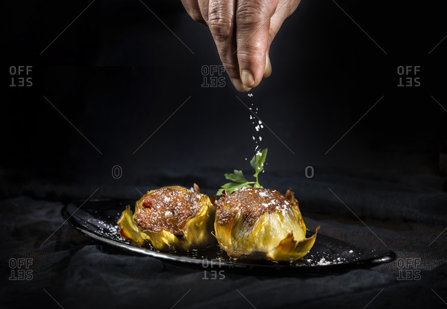 Crop hand of person sprinkling tasty stuffed artichokes with salt on black background